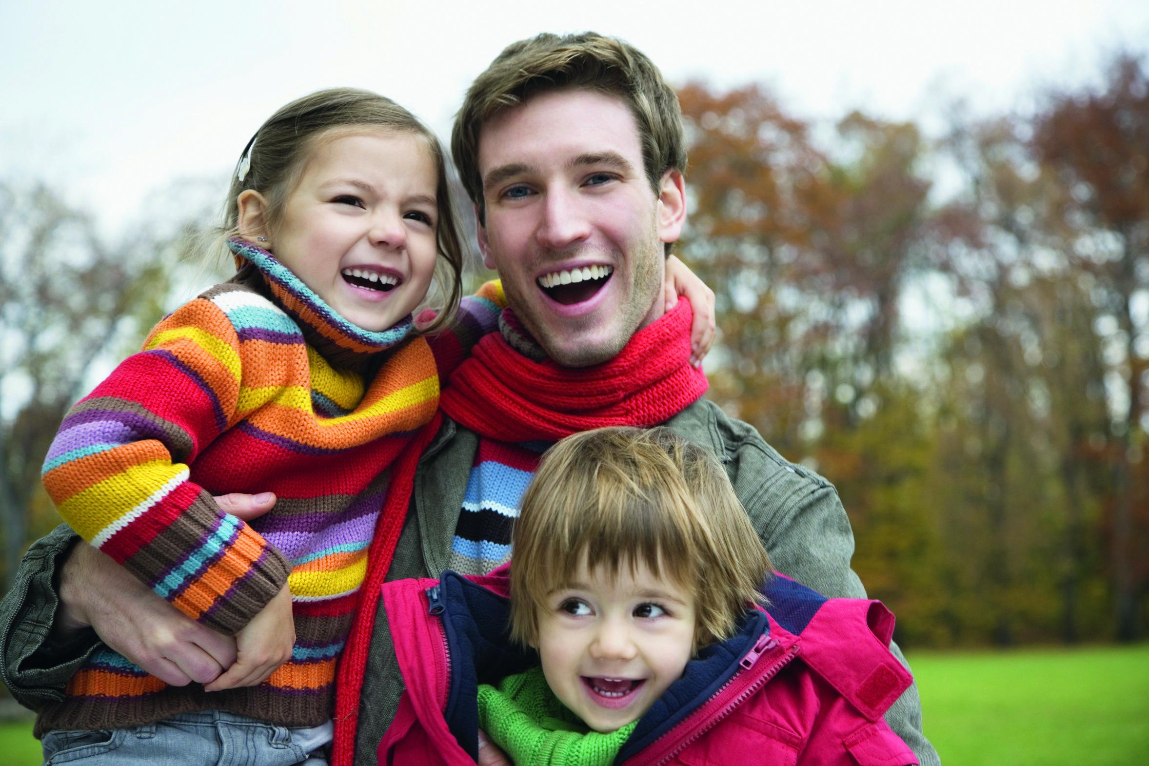Vater hält seine Kinder im Herbst